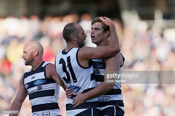 Tom Hawkins of the Cats is embraced by James Podsiadly and Paul Chapman after kicking a goal during the round 23 AFL match between the Geelong Cats...