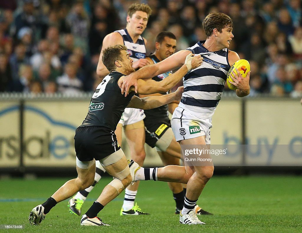 Tom Hawkins of the Cats is tackled by Robbie Gray of the Power during the Second Semi Final match between the Geelong Cats and the Port Adelaide Power at Melbourne Cricket Ground on September 13, 2013 in Melbourne, Australia.