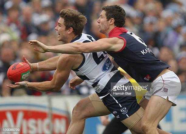 Tom Hawkins of the Cats marks under pressure from James Frawley of the Demons during the round 19 AFL match between the Geelong Cats and the...