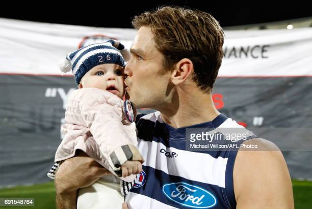 Tom Hawkins of the Cats runs onto the field for his 200th match with daughter Arabella during the 2017 AFL round 11 match between the Geelong Cats...