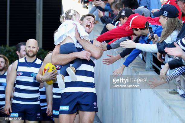 Tom Hawkins of the Cats walks out to play his 250th match with his daughter during the round 19 AFL match between the Sydney Swans and the Geelong...