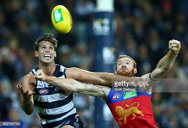 Tom Hawkins of the Geelong Cats takes a mark in front of Daniel Merrett of the Lions during the round three AFL match between the Geelong Cats and...