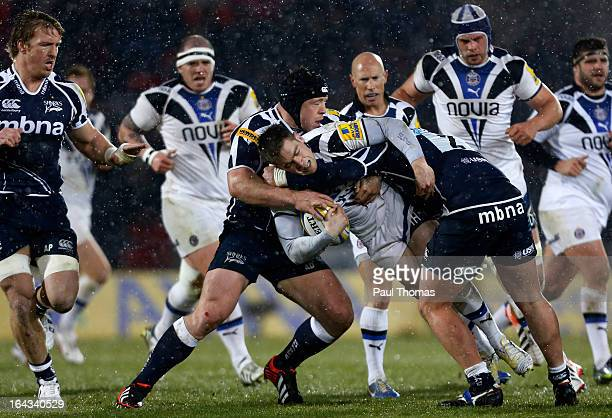 Tom Heathcote of Bath is tackled by Alasdair Dickinson and Marc Jones of Sale during the Aviva Premiership match between Sale Sharks and Bath Rugby...