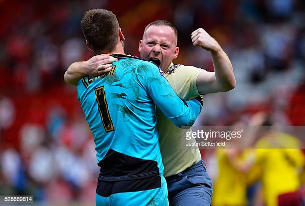 Tom Heaton of Burnley celebrates with a fan who ran on the pitch at the final whistle during the Sky Bet Championship between Charlton Athletic and...