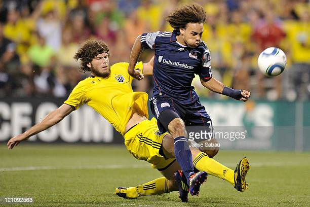 Tom Heinemann of the Columbus Crew reaches through the legs of Kevin Alston of the New England Revolution to kick the ball in for the Crew's first...