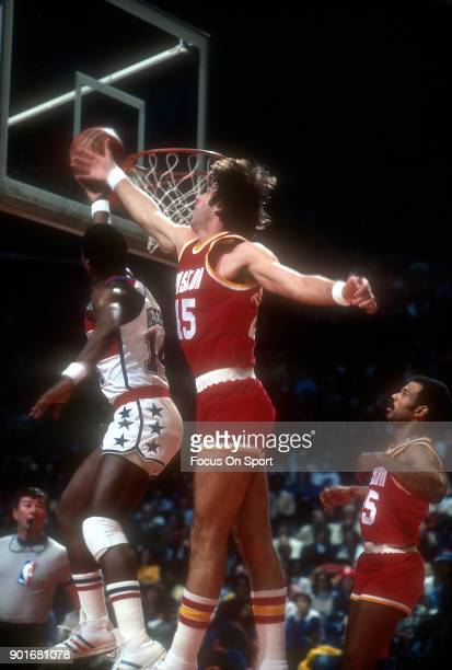 Tom Henderson of the Washington Bullets lays the ball up over Rudy Tomjanovich of the Houston Rockets during an NBA basketball game circa 1977 at the...