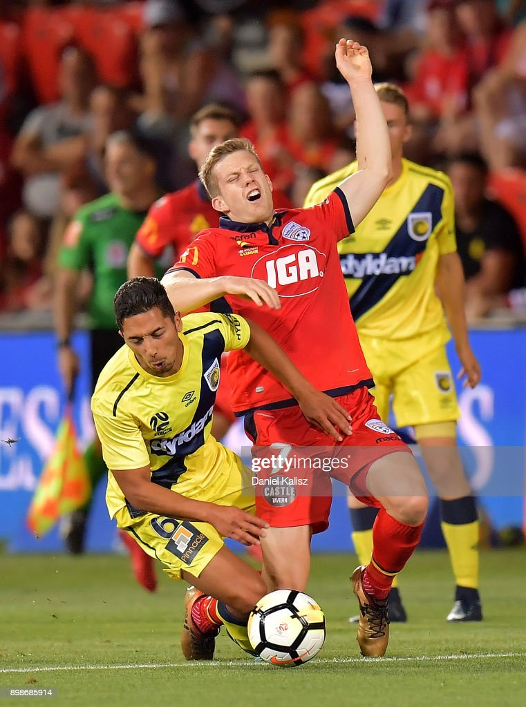 Tom Hiariej of the Mariners and Ryan Kitto of United compete for the ball during the round 12 A-League match between Adelaide United and the Central Coast Mariners at Coopers Stadium on December 26, 2017 in Adelaide, Australia.
