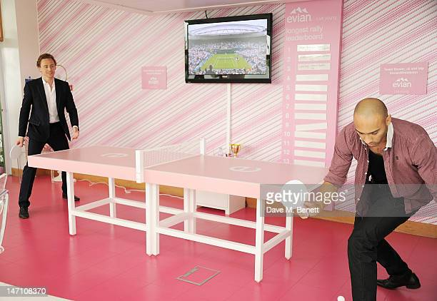 Tom Hiddleston and Alex Lanipekun play table tennis at the evian 'Live young' VIP Suite at Wimbledon on June 25 2012 in London England