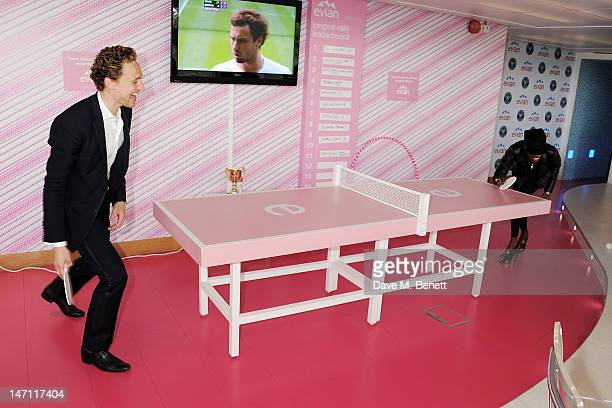 Tom Hiddleston and Grace Jones play table tennis at the evian 'Live young' VIP Suite at Wimbledon on June 25, 2012 in London, England.