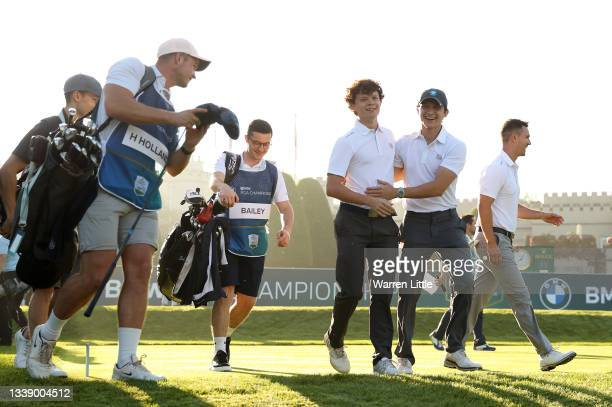 Tom Holland and Harry Holland interact as they leave the first tee during Previews ahead of The BMW PGA Championship at Wentworth Golf Club on...