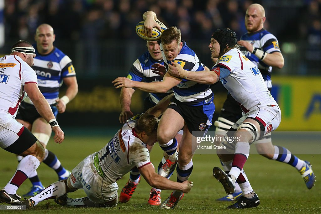 Tom Homer of Bath is held up by David Seymour (L) and Magnus Lund (R) of Sale during the Aviva Premiership match between Bath Rugby and Sale at the Recreation Ground on March 6, 2015 in Bath, England.