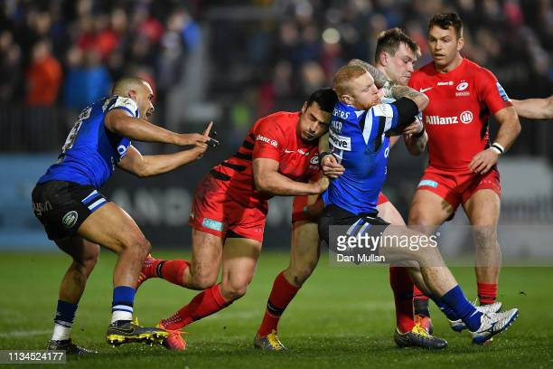 Tom Homer of Bath Rugby is tackled by Nick Tompkins and Alex Lozowski of Saracens during the Gallagher Premiership Rugby match between Bath Rugby and...