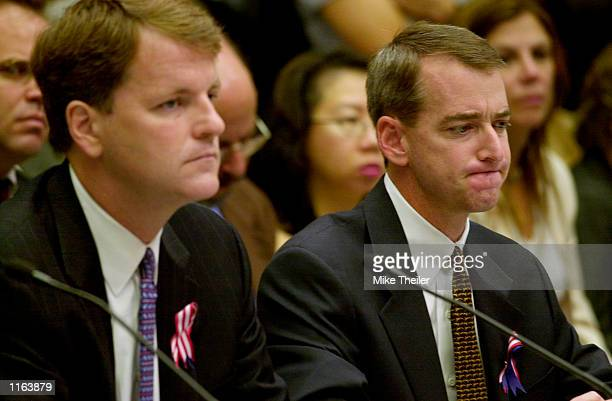 Tom Horton chief financial officer of American Airlines grimaces as he listens along with American West Airlines President and CEO Douglas Parker to...