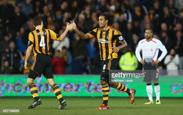 Tom Huddlestone of Hull City celebrates his team's third goal an own goal by Martin Skrtel of Liverpool with Alex Bruce during the Barclays Premier...