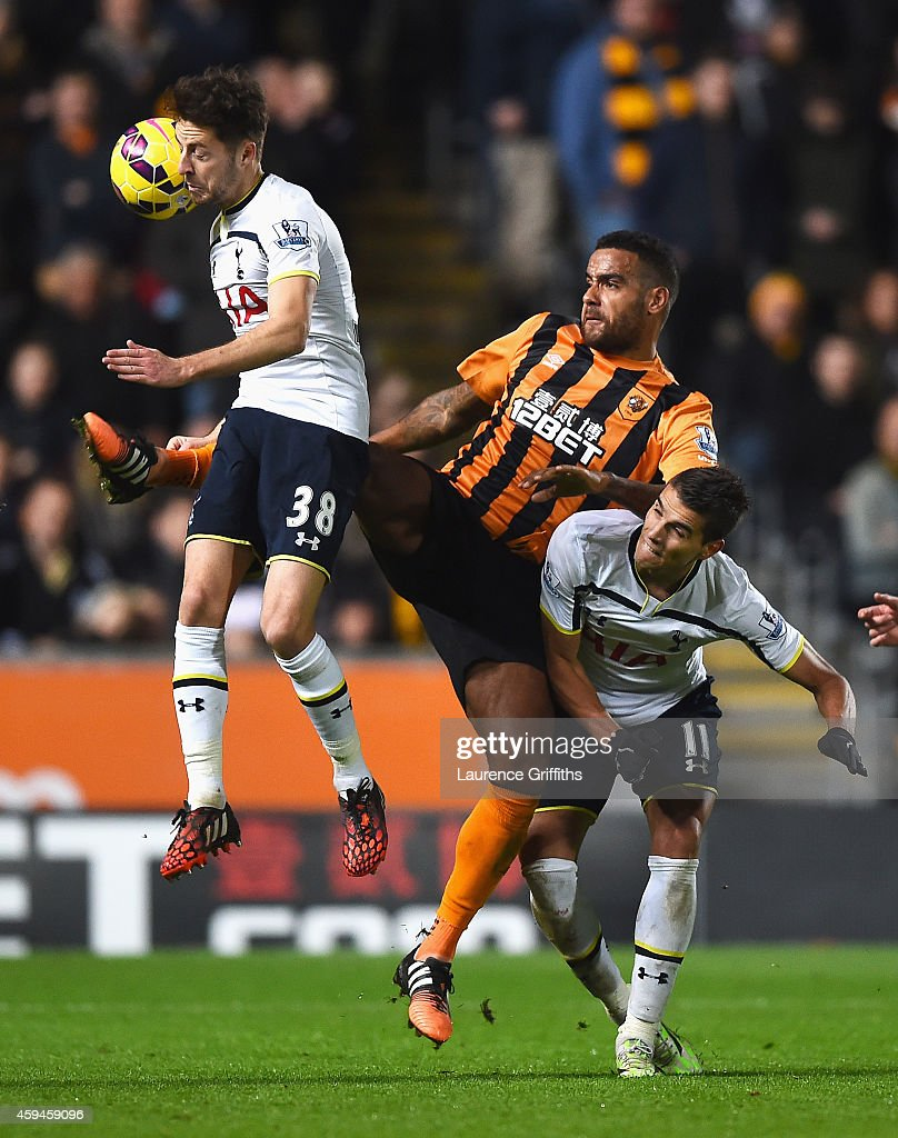 Tom Huddlestone of Hull City challenges Ryan Mason (L) and Erik Lamela of Tottenham Hotspur during the Barclays Premier League match between Hull City and Tottenham Hotspur at KC Stadium on November 23, 2014 in Hull, England.