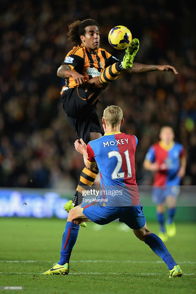 Tom Huddlestone of Hull City collects the ball as Dean Moxey of Crystal Palace looks on during the Barclays Premier League match between Hull City and Crystal Palace at KC Stadium on November 23, 2013 in Hull, England.