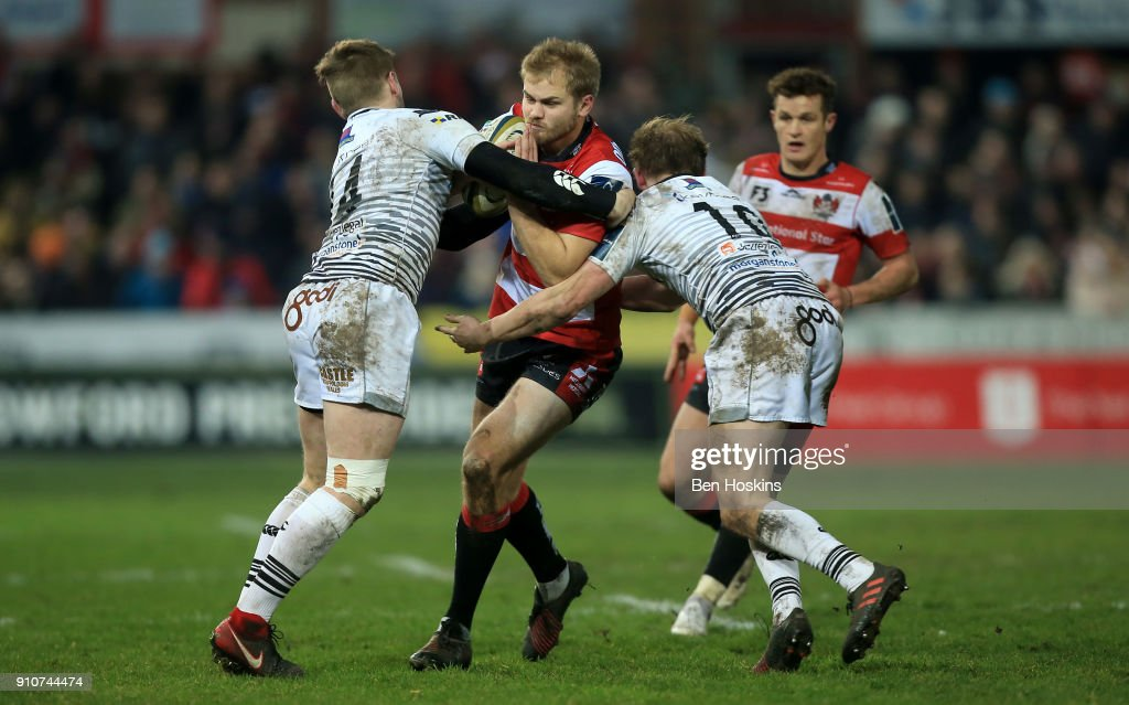 Tom Hudson of Gloucester is tackled by Dafydd Howells and Luke Price of Ospreys during the Anglo-Welsh Cup match between Gloucester Rugby and Ospreys at Kingsholm Stadium on January 26, 2018 in Gloucester, England.