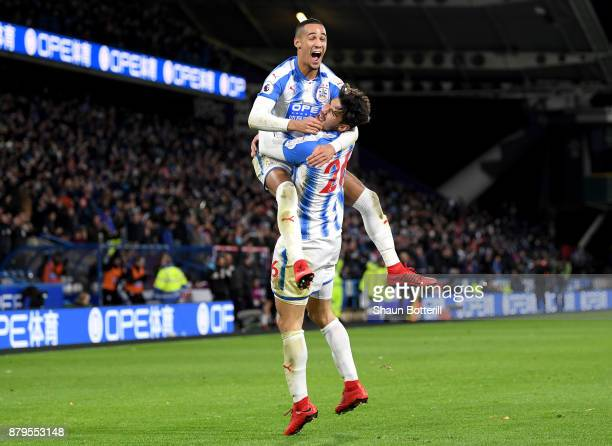 Tom Ince and Christopher Schindler of Huddersfield Town celebrate after Nicolas Otamendi of Manchester City scored the first own goal during the...