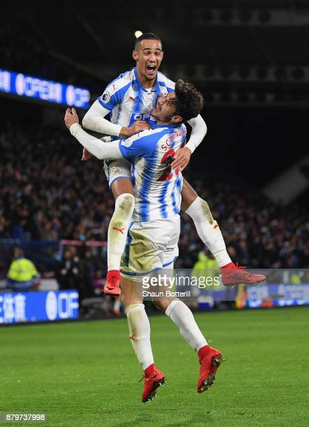 Tom Ince and Christopher Schindler of Huddersfield Town celebrate after Nicolas Otamendi of Manchester City scored the an own goal during the Premier...