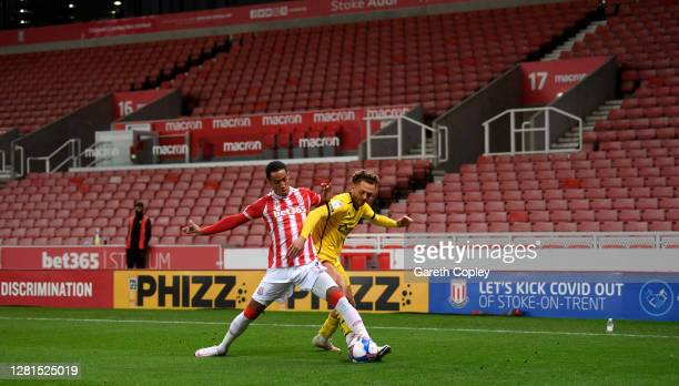 Tom Ince of Stoke City is tackled by Jordan Williams of Barnsley in front of Covid19 signage during the Sky Bet Championship match between Stoke City...