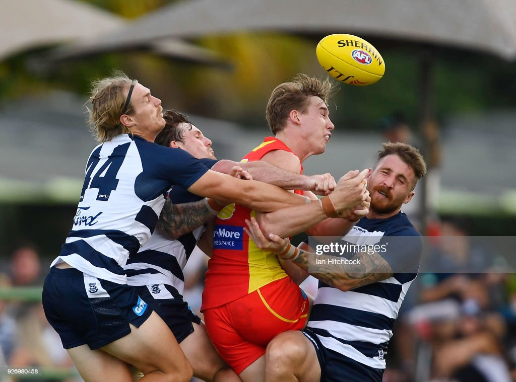 Tom J. Lynch of the Suns is crunched in a tackle by Jed Bews, Tom Stewart and Zach Tuohy of the Cats during the AFL JLT Community Series match between the Geelong Cats and the Gold Coast Suns at Riverway Stadium on March 4, 2018 in Townsville, Australia.