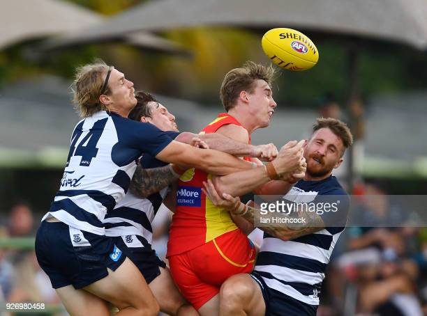 Tom J Lynch of the Suns is crunched in a tackle by Jed Bews Tom Stewart and Zach Tuohy of the Cats during the AFL JLT Community Series match between...