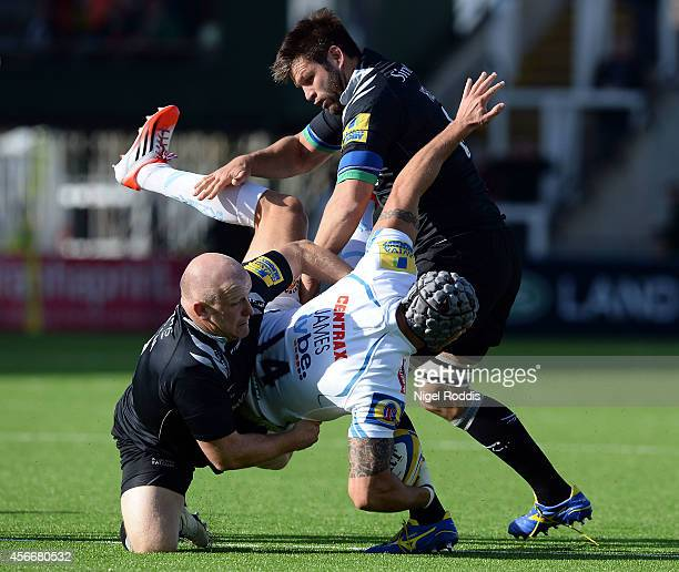 Tom James of Exeter Chiefs tackled by Scott Lawson and Ally Hogg of Newcastle Falcons ahead of the Aviva Premiership match between Newcastle Falcons...