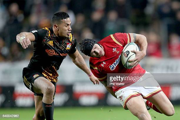 Tom James of Wales is tackled by Toni Pulu of the Chiefs during the International Test match between the Chiefs and Wales at Waikato Stadium on June...