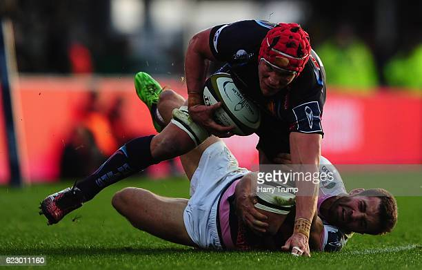 Tom Johnson of Exeter Chiefs is tackled by James Beal of Cardiff Blues during the AngloWelsh Cup match between Exeter Chiefs and Cardiff Blues at...