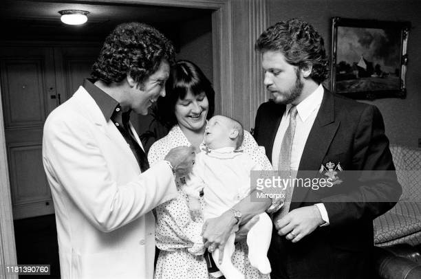 Tom Jones with his grandson Alexander, aged eleven months, son Mark Woodward and daughter-in-law Donna in their London hotel. 3rd September 1983.