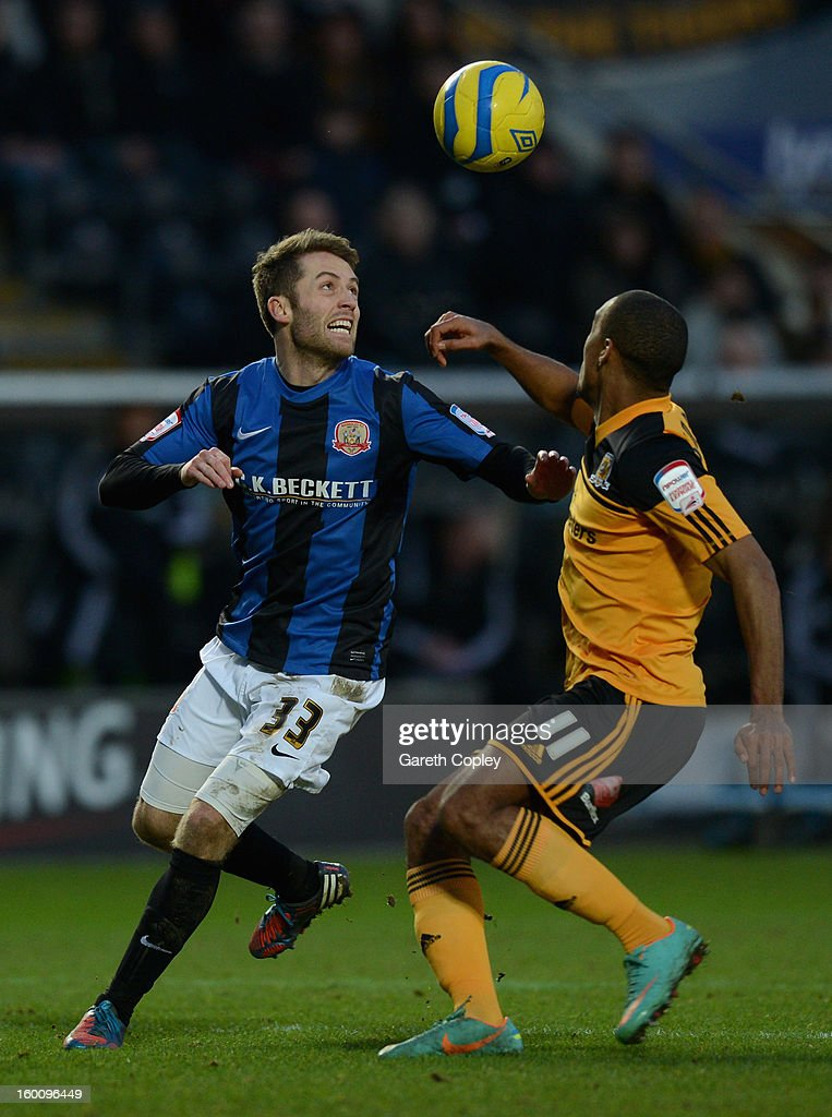 Tom Kennedy of Barnsley and Jay Simpson of Hull City challenge for the ball during the FA Cup Fourth Round between Hull City and Barnsley at KC Stadium on January 26, 2013 in Hull, England.