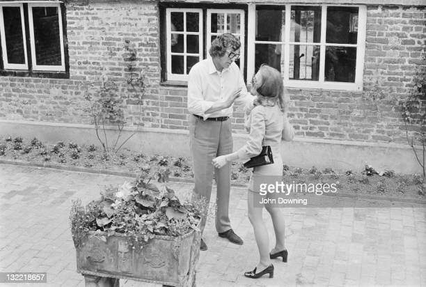 Tom Keylock chauffeur and 'fixer' for the Rolling Stones talking to a young woman possibly Janet Lawson at Cotchford Farm in East Sussex 3rd July...