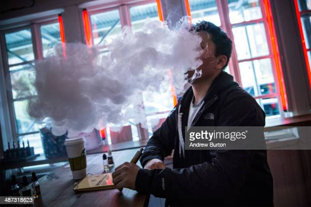Tom Kim vapes or smokes an electronic cigarette at Henley Vaporium on April 29 2014 in New York City A new law that goes into effect today in New...