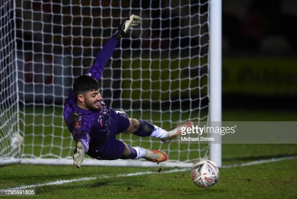 Tom King of Newport County saves a penalty from Neal Maupay of Brighton and Hove Albion in the shootout during the FA Cup Third Round match between...