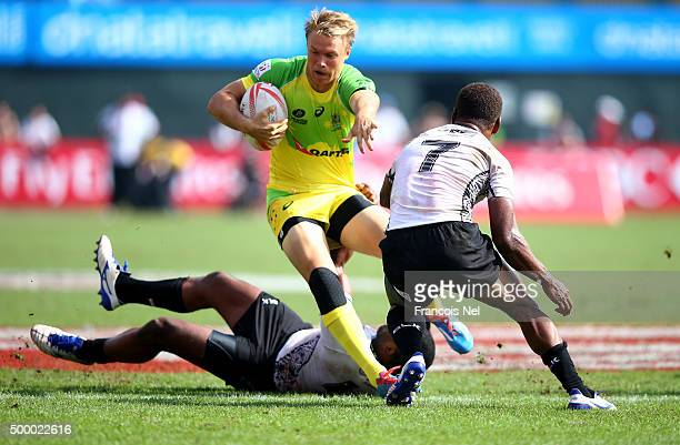 Tom Kingston of Australia is tackled by Osea Kolinisau and Isake Katonibau of Fiji during the Emirates Dubai Rugby Sevens HSBC World Rugby Sevens...