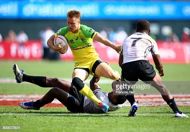 Tom Kingston of Australia is tackled by Osea Kolinisau and Isake Katonibau of Fiji during the Emirates Dubai Rugby Sevens - HSBC World Rugby Sevens...