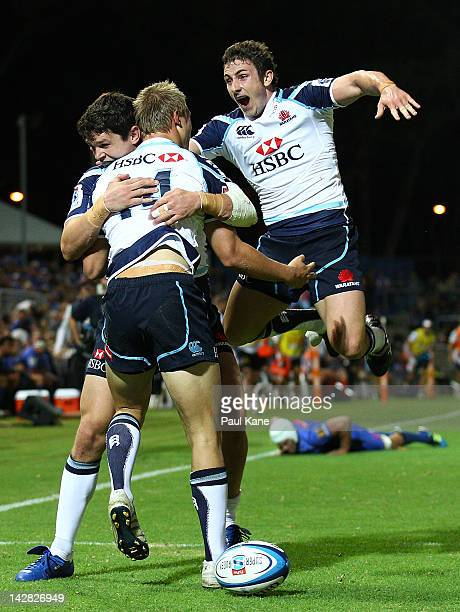 Tom Kingston of the Waratahs is congratulated by Tom Carter and Brendan McKibbin after scoring a try during the round seven Super Rugby match between...