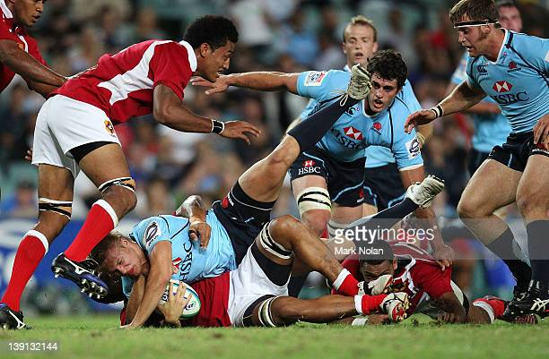 Tom Kingston of the Waratahs is tackled during the Super Rugby trial match between the Waratahs and Tonga at Sydney Football Stadium on February 17...