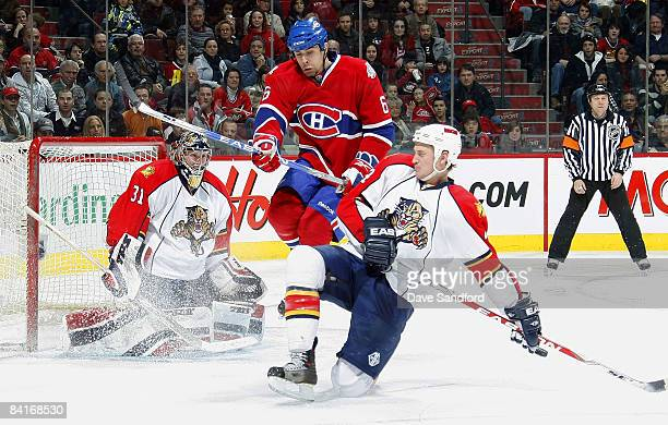 Tom Kostopoulos of the Montreal Canadiens leaps through the crease as Craig Anderson of the Florida Panthers moves into position while his teammate...