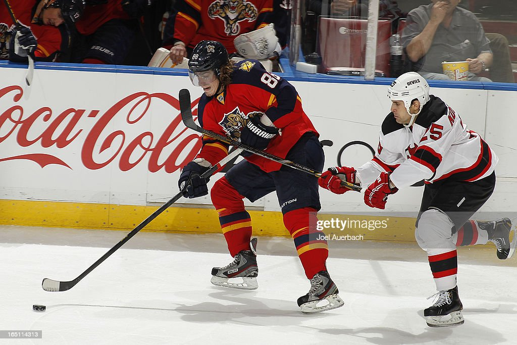 Tom Kostopoulos #25 of the New Jersey Devils checks Peter Mueller #88 of the Florida Panthers as he skates up ice with the puck at the BB&T Center on March 30, 2013 in Sunrise, Florida. The Panthers defeated the Devils 3-2 in overtime.