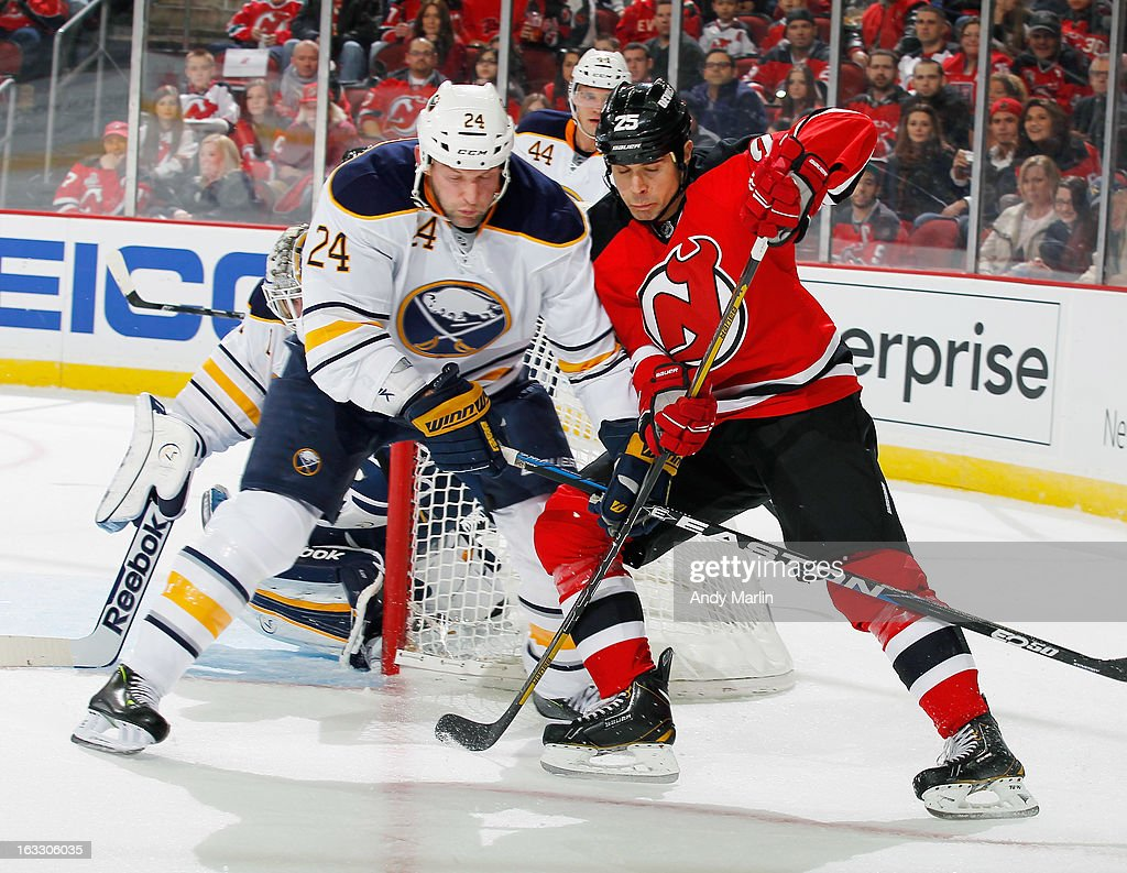 Tom Kostopoulos #25 playing in his first game as a New Jersey Devil battles for position against Robyn Regehr #24 of the Buffalo Sabres during the game at the Prudential Center on March 7, 2013 in Newark, New Jersey.