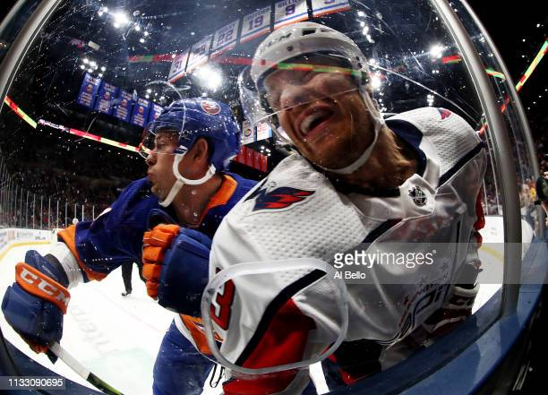 Tom Kuhnhackl of the New York Islanders checks Nick Jensen of the Washington Capitals during their game at NYCB Live's Nassau Coliseum on March 01...