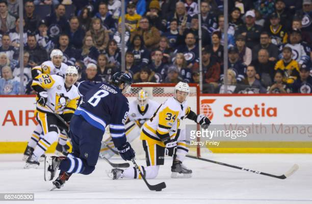 Tom Kuhnhackl of the Pittsburgh Penguins gets set to block a shot off the point by Jacob Trouba of the Winnipeg Jets during first period action at...