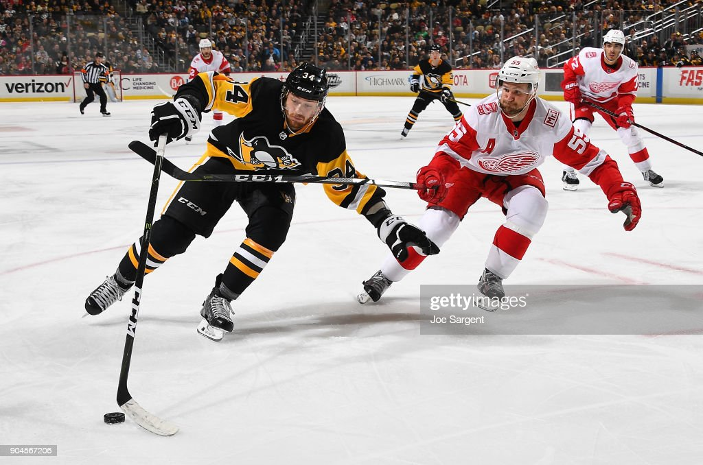 Tom Kuhnhackl #34 of the Pittsburgh Penguins handles the puck against Niklas Kronwall #55 of the Detroit Red Wings at PPG Paints Arena on January 13, 2018 in Pittsburgh, Pennsylvania.