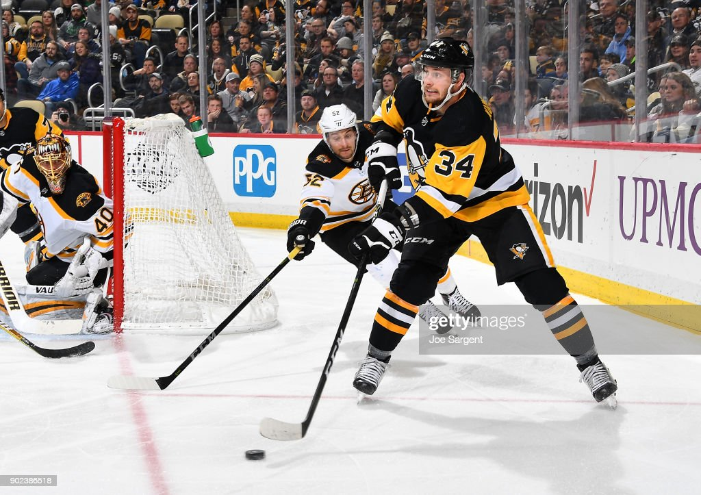 Tom Kuhnhackl #34 of the Pittsburgh Penguins moves the puck in front of Sean Kuraly #52 of the Boston Bruins at PPG Paints Arena on January 7, 2018 in Pittsburgh, Pennsylvania.
