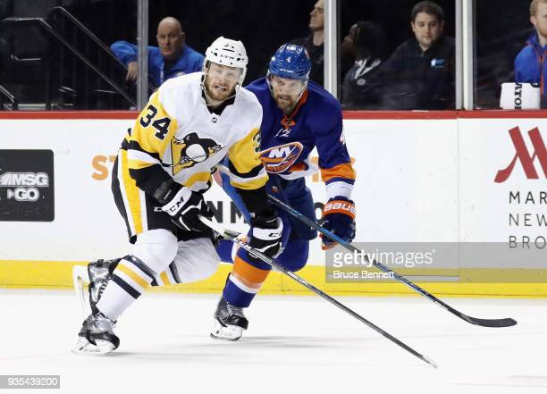 Tom Kuhnhackl of the Pittsburgh Penguins skates against Dennis Seidenberg the New York Islanders at the Barclays Center on March 20 2018 in the...