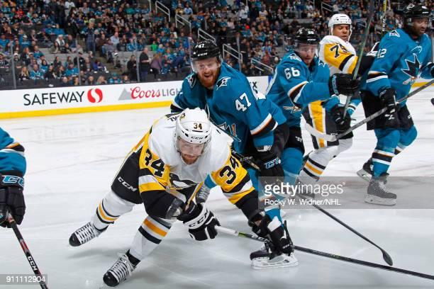 Tom Kuhnhackl of the Pittsburgh Penguins skates againt Joakim Ryan of the San Jose Sharks at SAP Center on January 20 2018 in San Jose California