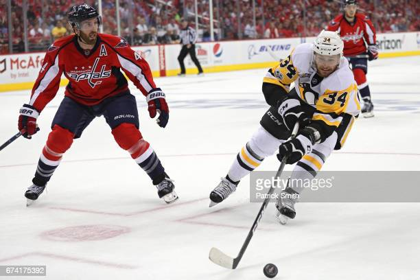 Tom Kuhnhackl of the Pittsburgh Penguins skates with the puck past Brooks Orpik of the Washington Capitals in the first period in Game One of the...
