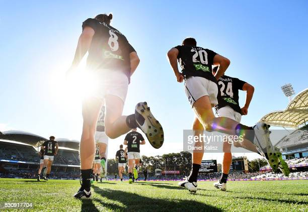 Tom Langdon, Ben Reid and Josh Thomas of the Magpies run out onto the ground for their warm up prior to the round 21 AFL match between Port Adelaide...