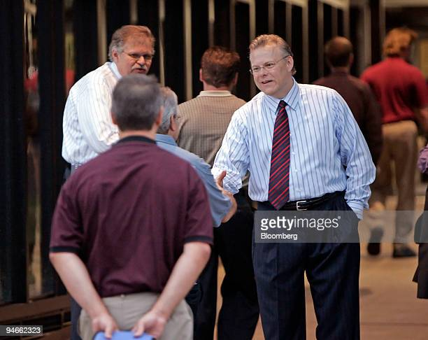 Tom LaSorda, vice chairman and president of Chrysler LLC, right, greets employees arrriving for work at the company's headquarters in Auburn Hills,...